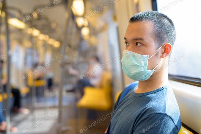 Face of young Asian man with mask sitting with distance inside the train