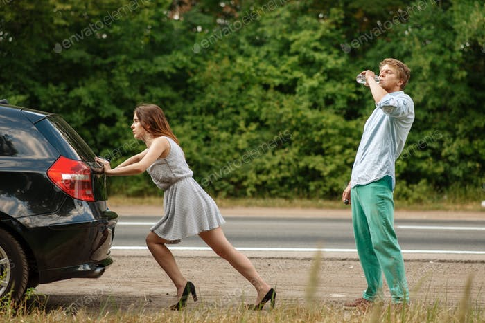 Man and woman pushing broken car on road
