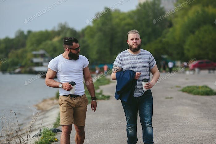 Two men walk and drink coffee