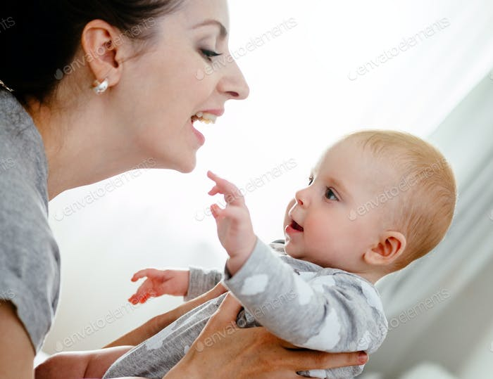 Happy smiling mother and baby playing on bed at home. Happy family having fun.