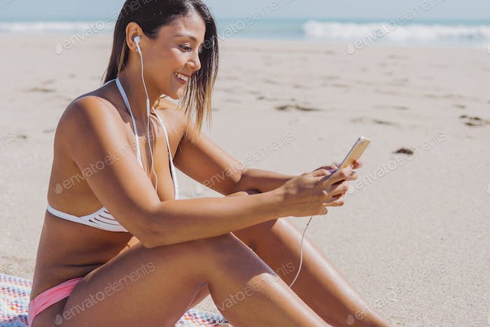 Woman smiling and texting on beach