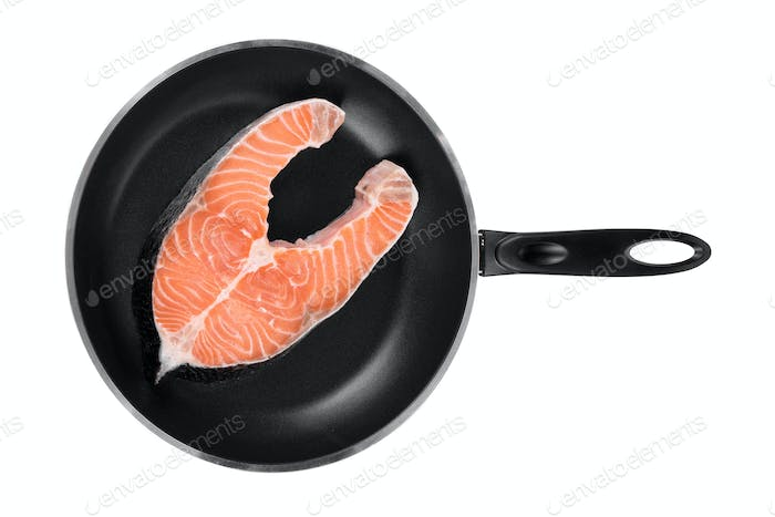 Salmon steak on frying pan.
