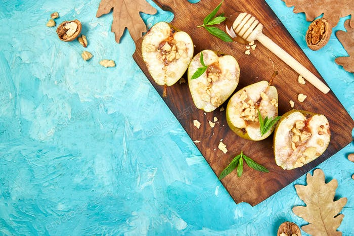 Tasty roast pears with honey and walnuts on blue background table.