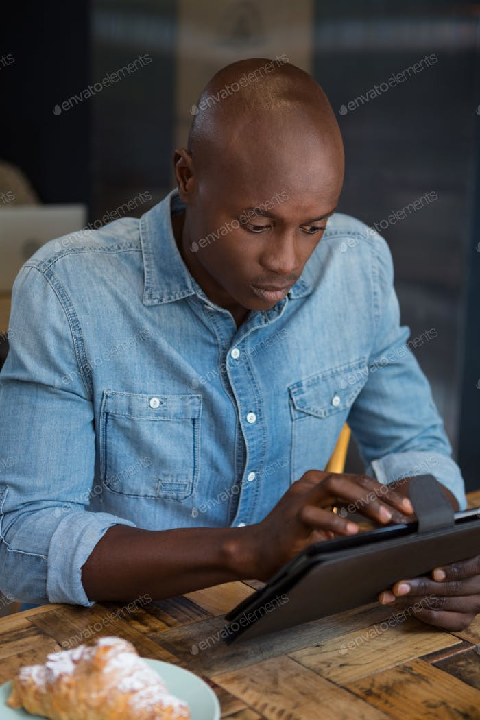 Man using digital tablet at wooden table in coffee house