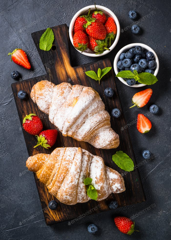 Croissant with fresh berries on black background
