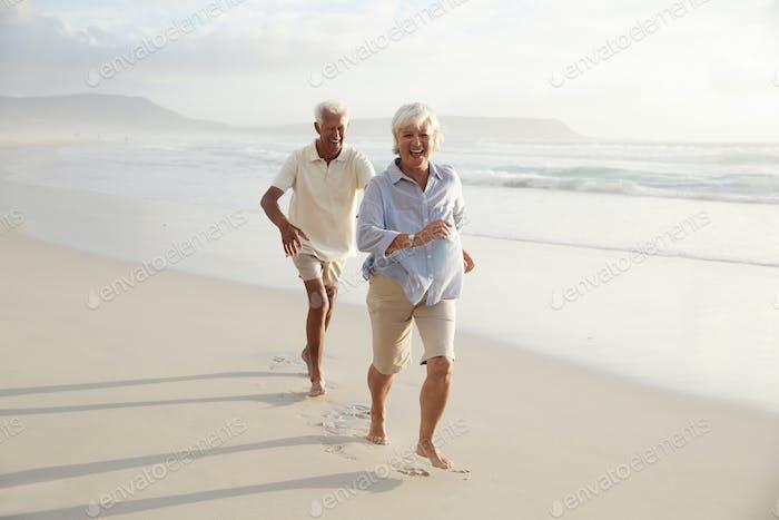 Senior Retired Couple Running Along Summer Beach Together