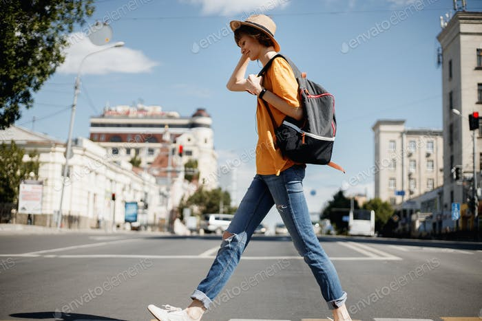 Junges Mädchen mit Kopfhörern in einem gelben T-Shirt und einem Strohhut überquert die Straße mit einem Rucksack in