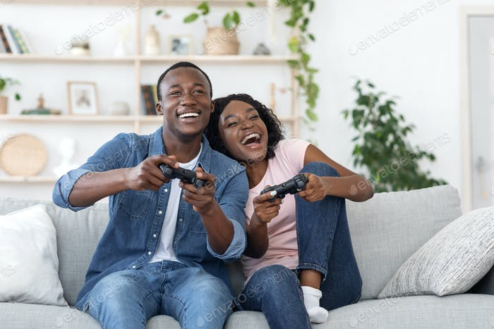 Emotional african family playing video games at living room