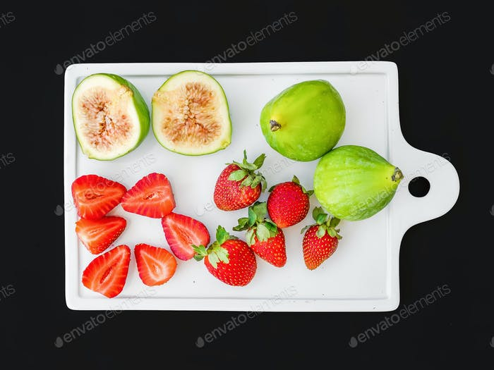 A set of fresh fruit on a white ceramic cutting board