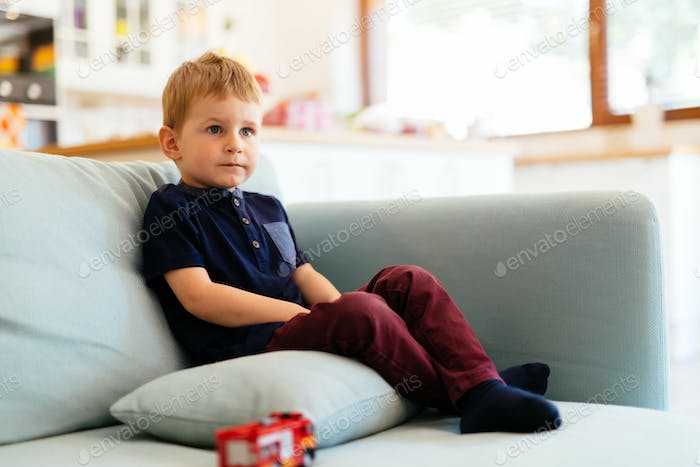 Happy boy sitting on living room couch