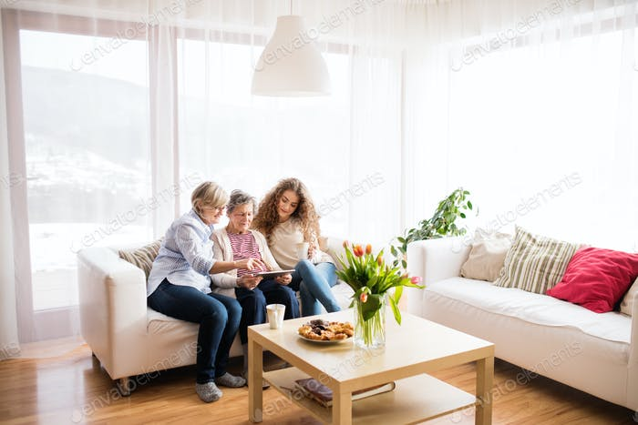 A teenage girl, mother and grandmother with tablet at home.