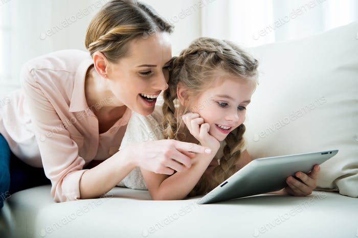 portrait of cheerful mother and daughter using tablet at home