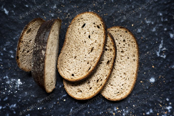 Slices of wheat loaf with black background