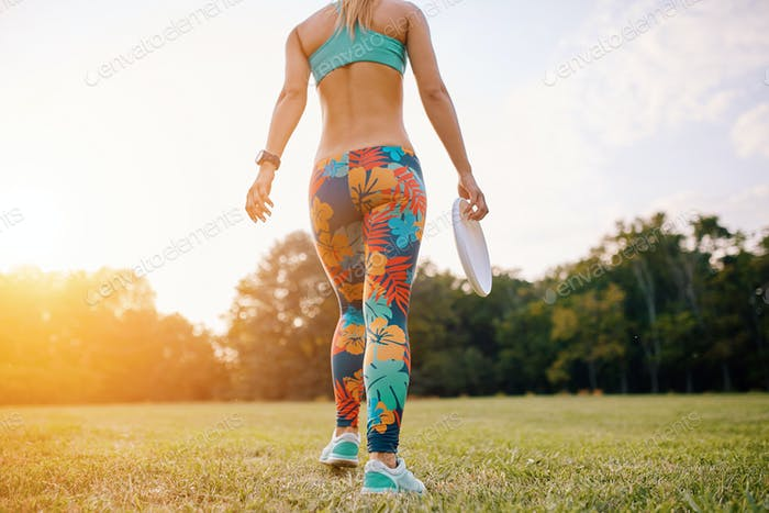 Young athletic girl playing with flying disc, ultimate