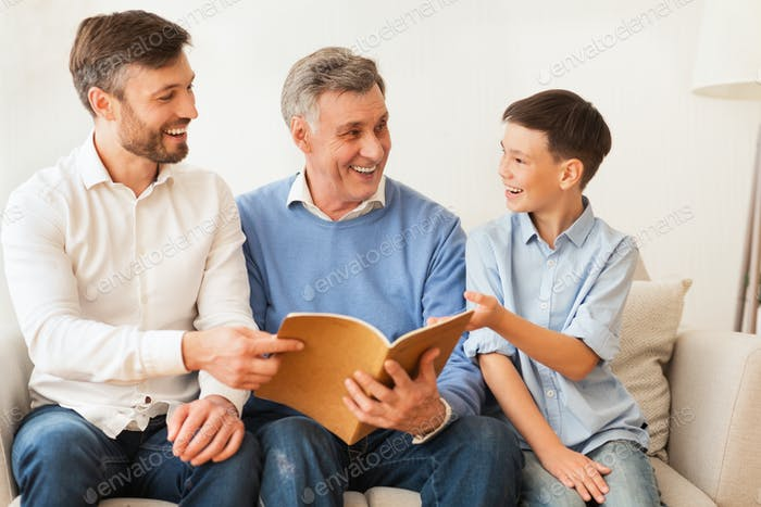 Son, Father And Grandfather Reading Book Sitting On Sofa Indoor