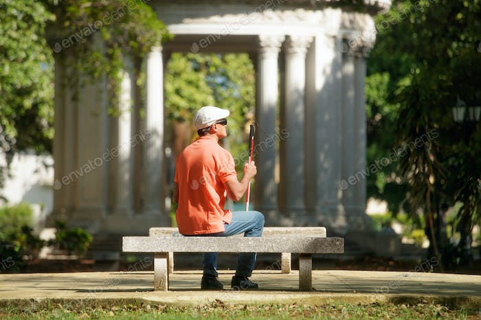 Blind Man Sitting In City Park And Resting