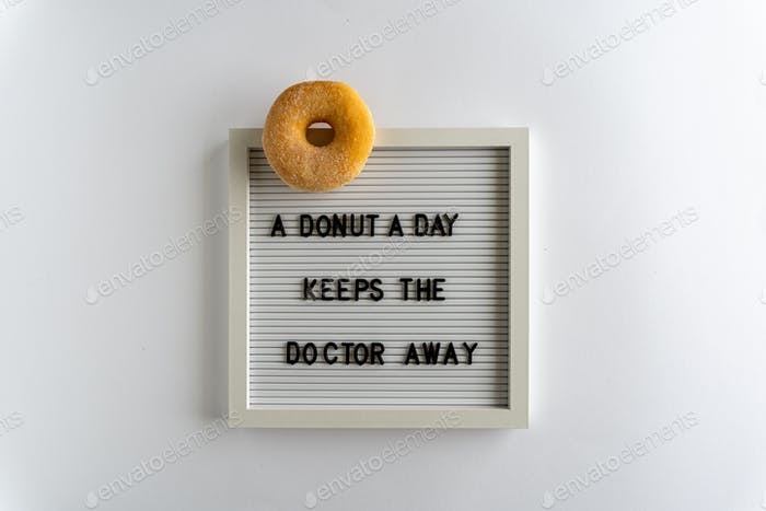 Letterboard With Words That Spell A Donut A Day Keeps The Doctor Away, with a donut , on a white