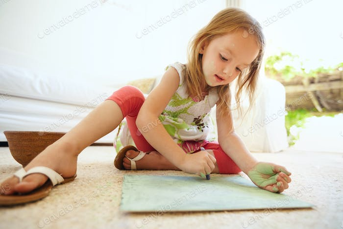 Little baby girl coloring picture at home