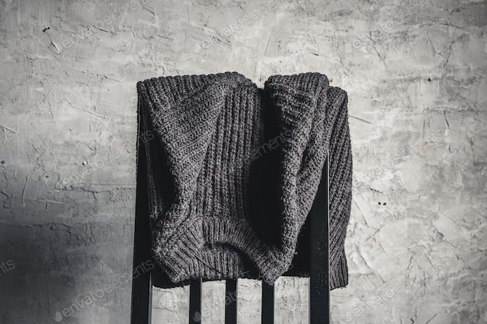 Knitted gray sweater on the back of a white wooden chair