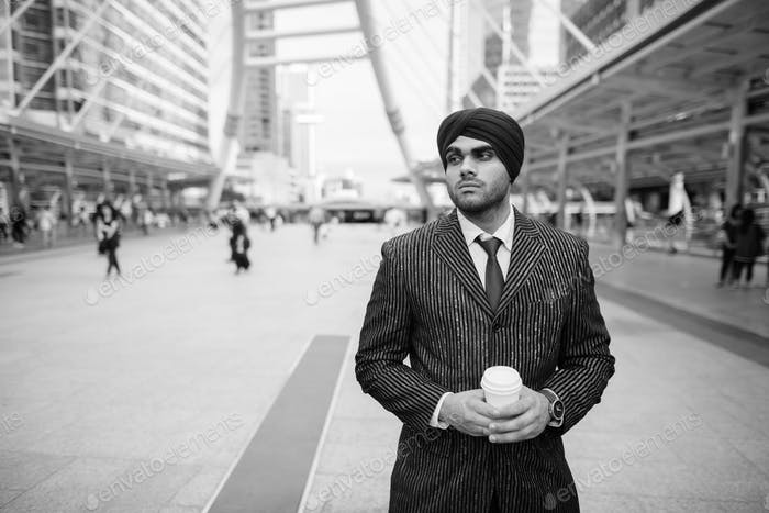 Young handsome Indian Sikh businessman wearing turban in the city