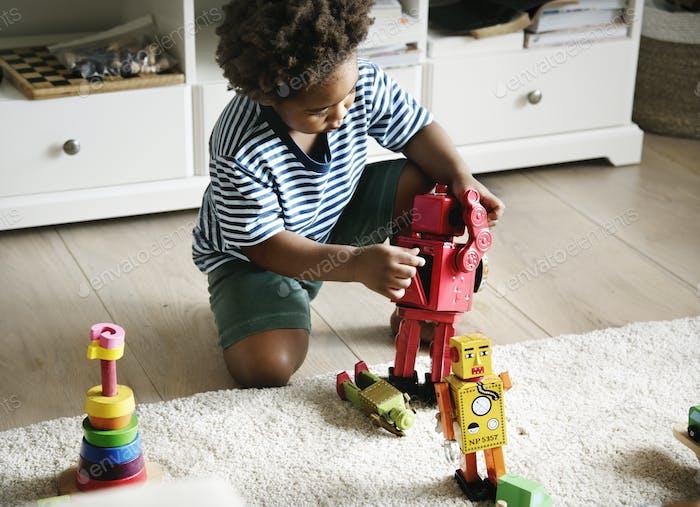 Black boy playing robot at home