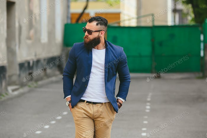 Stylish bearded man walks through the city