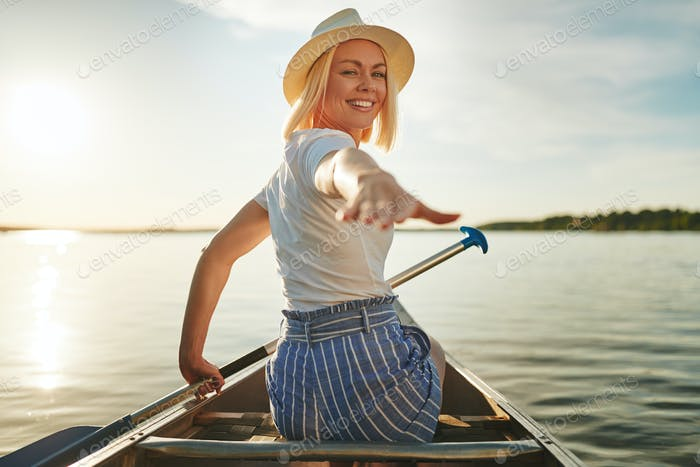 Smiling woman canoeing on a scenic lake in the summer