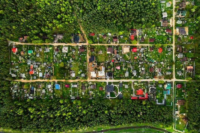Аэрофотосъемка сверху жилого дачного поселка в лесу Пригородная недвижимость в