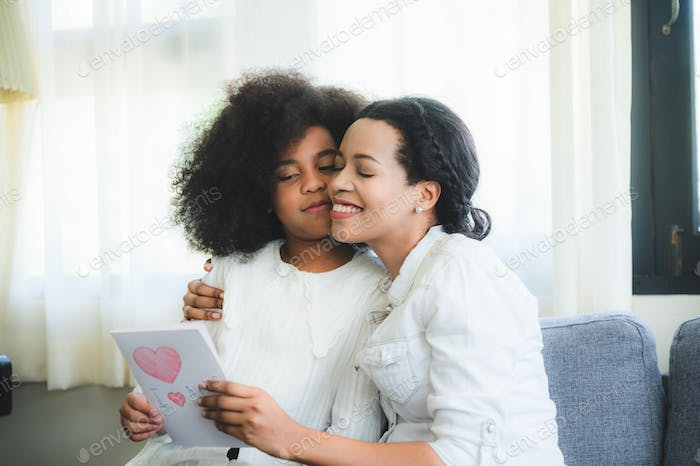 mother family together at living room home house, son give mom a card on mother's day