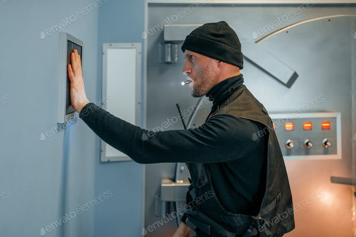 Robber in uniform trying to open the vault door