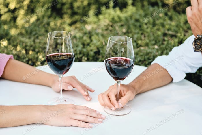 Close up couple with glasses of red wine on romantic date in restaurant outdoor