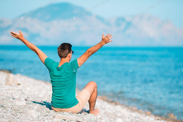 Young man on the white beach on vacation
