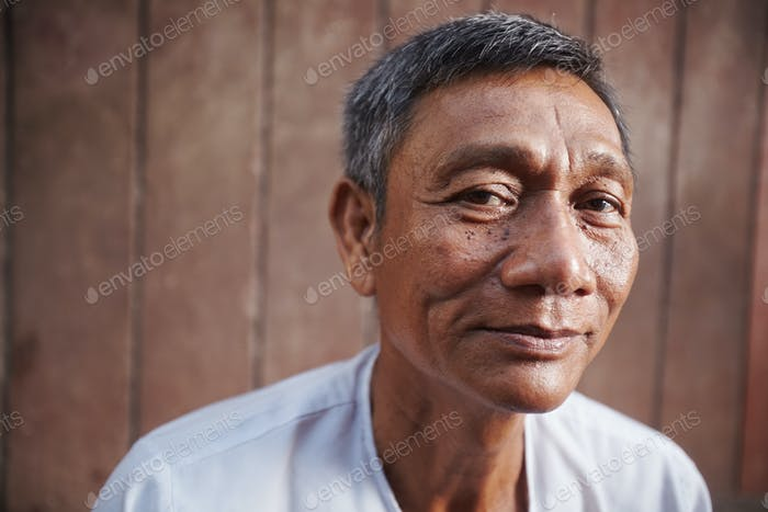 Asian Old Man Looking At Camera Against Brown Wall