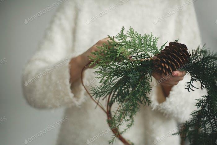 Rustic christmas wreath in female hands.