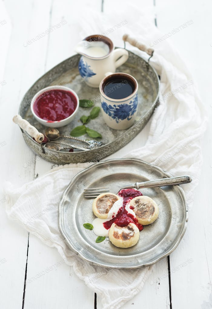 Rustic breakfast set. Russian cottage cheese pancakes or syrniki on a vintage metal plate
