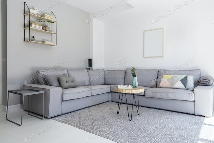 Grey corner sofa and wooden table in spacious living room interi