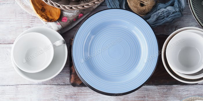 Ceramic and enamel crockery on wooden background