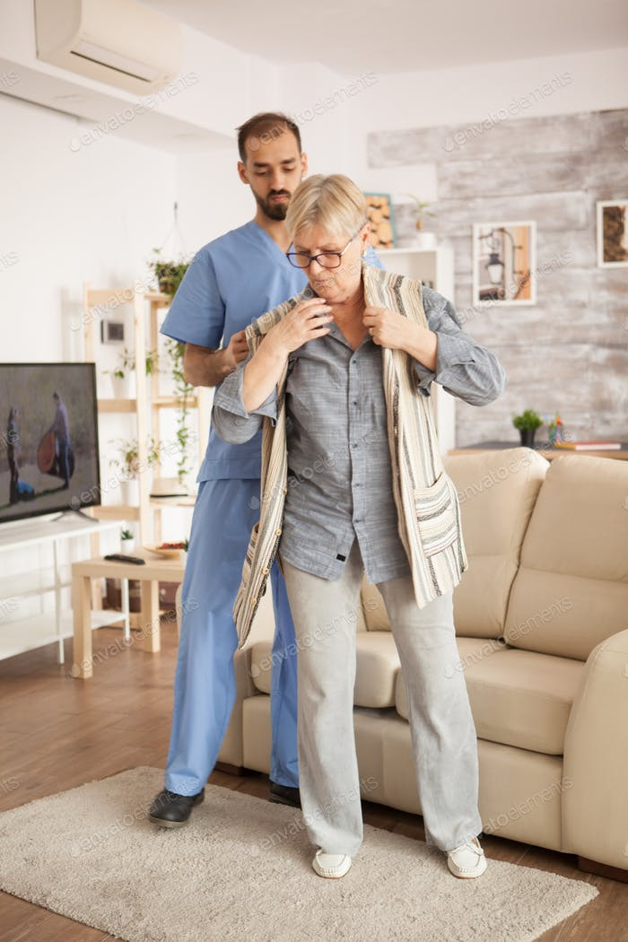 Male doctor in nursing home wearing blue uniform