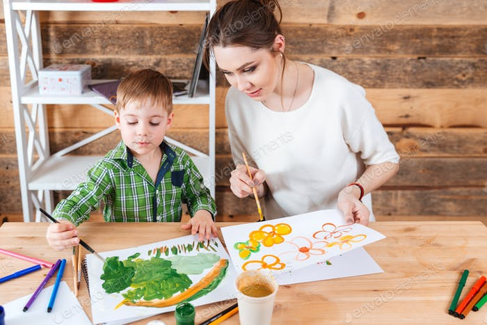 Cute little boy and his mother paiting bright pictures together
