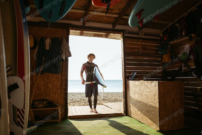 Sports man going to the beach shack with surf board