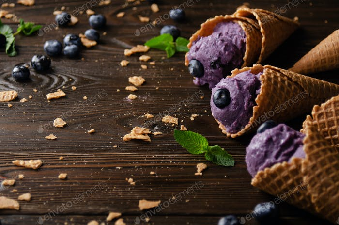 Wafer cones with blackberry icecream on wooden kitchen table with crumbs and berries aside