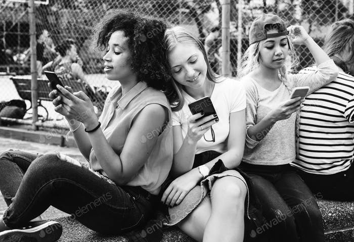 Friends in the park using smartphones and chilling