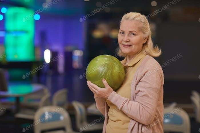 Retrato de mujer madura sosteniendo bola de bolos