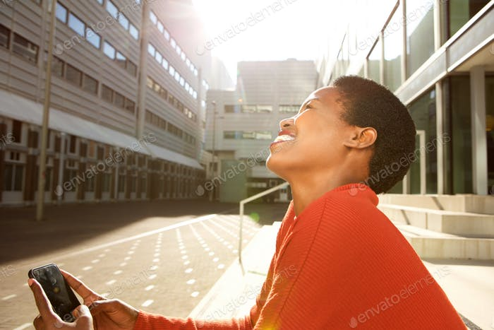 Profile of happy young african american woman sitting in city and looking at mobile phone