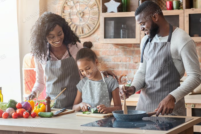 Girl making her first meal, spending time together with parents