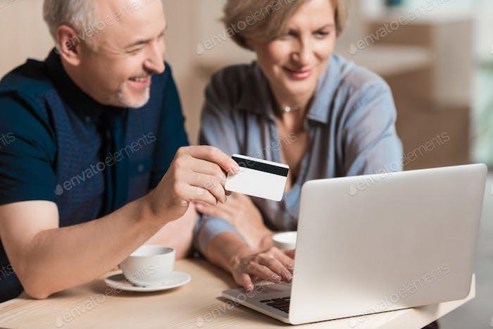 Schönes Paar möchte etwas online kaufen und mit Kreditkarte bezahlen