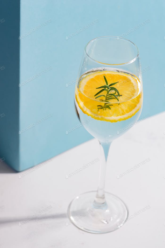 Summer homemade cold cocktail in a glass with lemon slice on a white table with shadow against