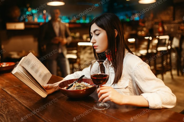 Woman reading a book at wooden bar counter