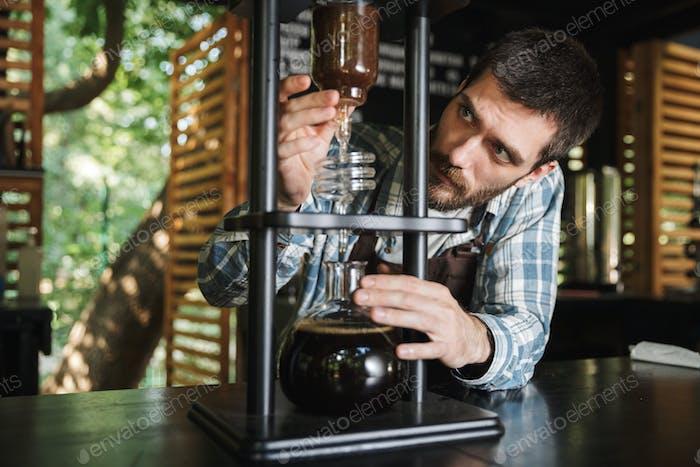 Bild der Brünette barista junge machen Kaffee während der Arbeit in caf