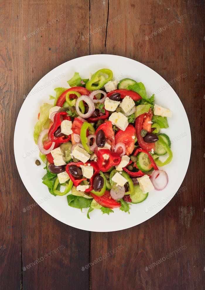 Greek salad with fresh vegetables and feta cheese background texture.